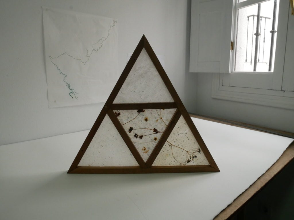 Wooden triangle made of four triangles with transparent paper and flowers inside, shown standing on a table in a room by a window.